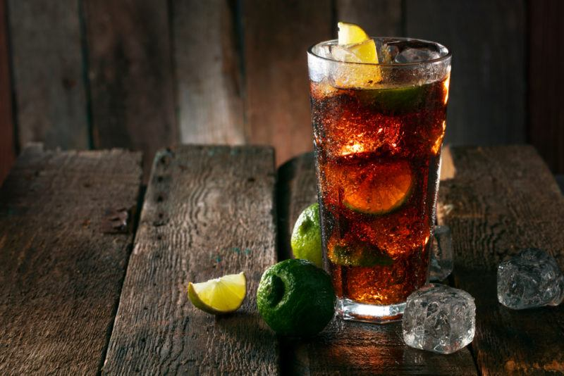 A rum and coke with ice and limes on a wooden table