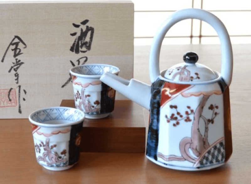 Old Imari with Handle Carafe Sake Setsitting on a wooden table with a wood sake set crate in the background