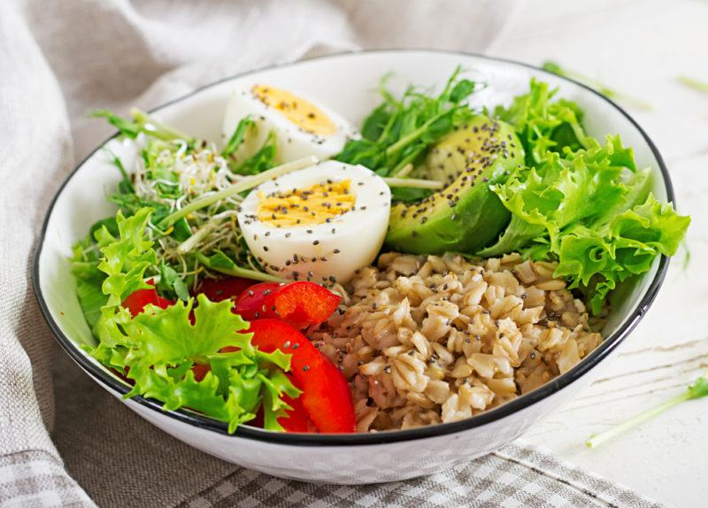A savory oatmeal bowl with eggs and lettuce as toppings