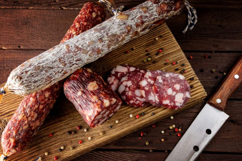 A wooden board with various types of fresh salami, peppercorns and a knife