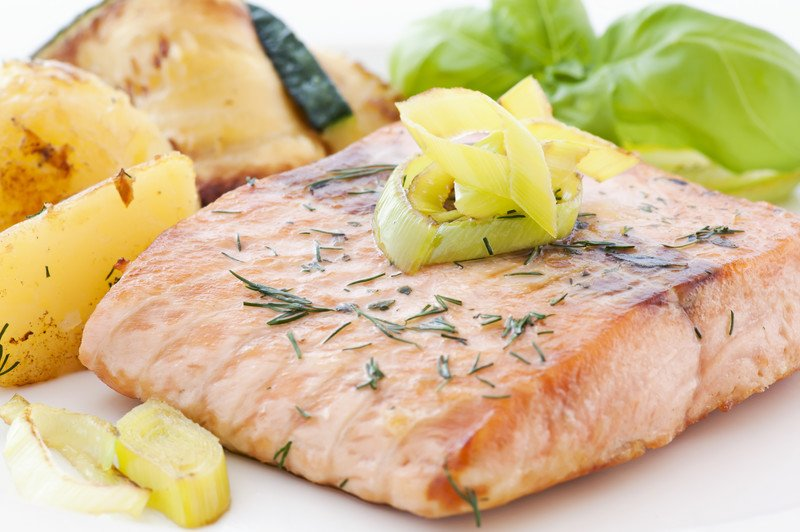A piece of cooked salmon garnished with onions rests on a white ceramic plate near roasted potatoes and a green leafy vegetable.
