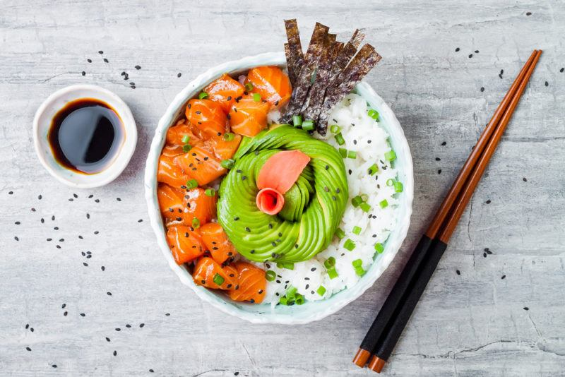 A salmon poke bowl that includes avocado, salmon, seaweed and rice
