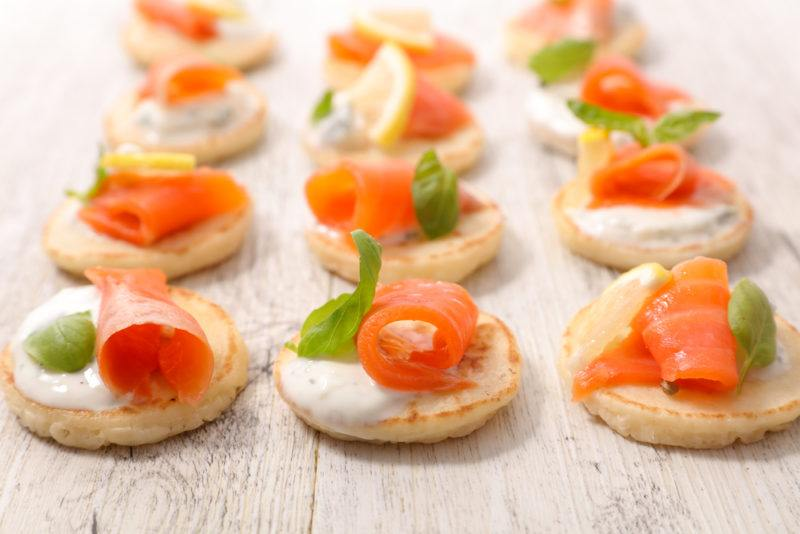 A table of some type that contains salmon and cream cheese canapes