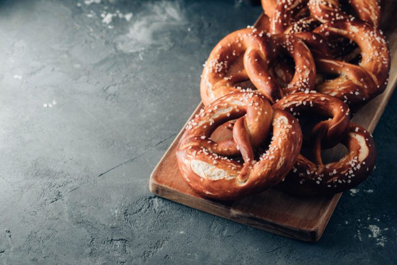 Fresh pretzels with salt on a wooden board that's on a gray table