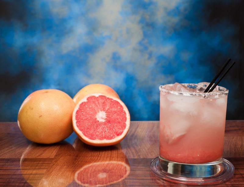 A grapefruit cocktail with grapefruit on a table