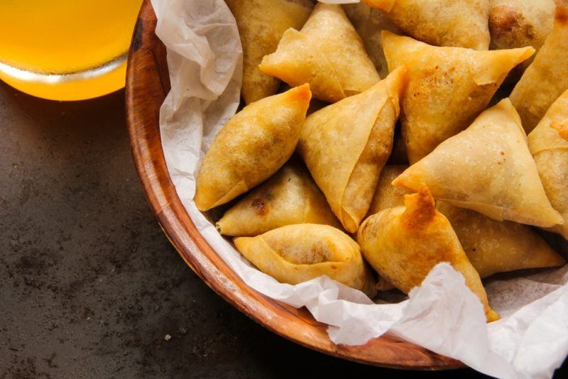 A brown bowl of samosas that have been cooked for a party
