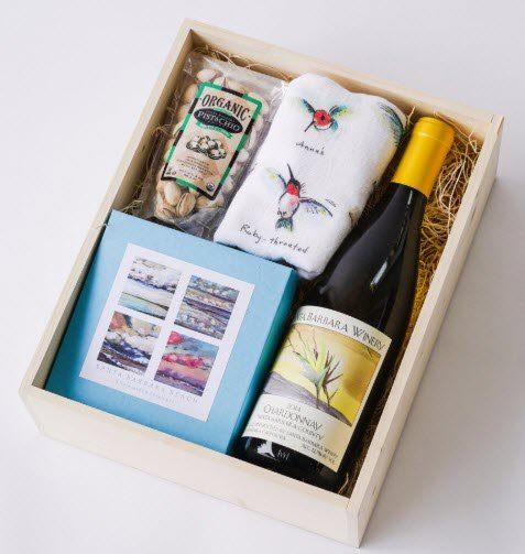 A wooden box with wine, a tea towel and some other items.