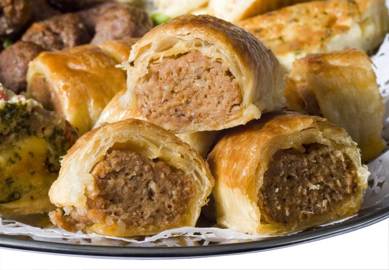 A pile of small sausage rolls on a plate