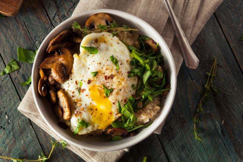A savory oatmeal bowl that includes an egg and greens
