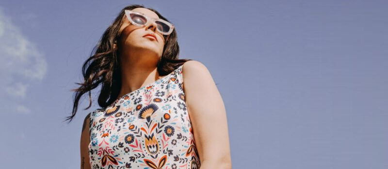 A woman in an interesting dress wearing glasses, standing outside and framed against the sky