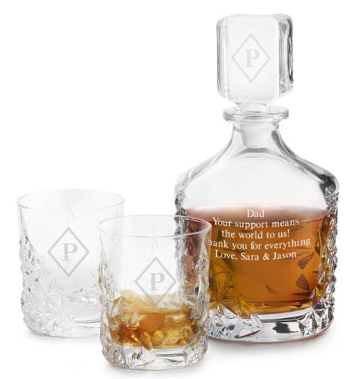 Whiskey decanter engraved with a quote, along with two glasses, one containing whiskey.