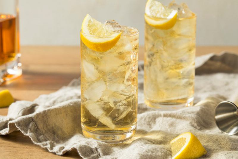 Two glasses of seven and seven cocktail with ice and lemons