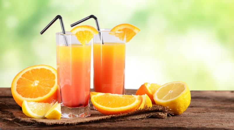 Two glasses of sex on the beach with sliced oranges and straws