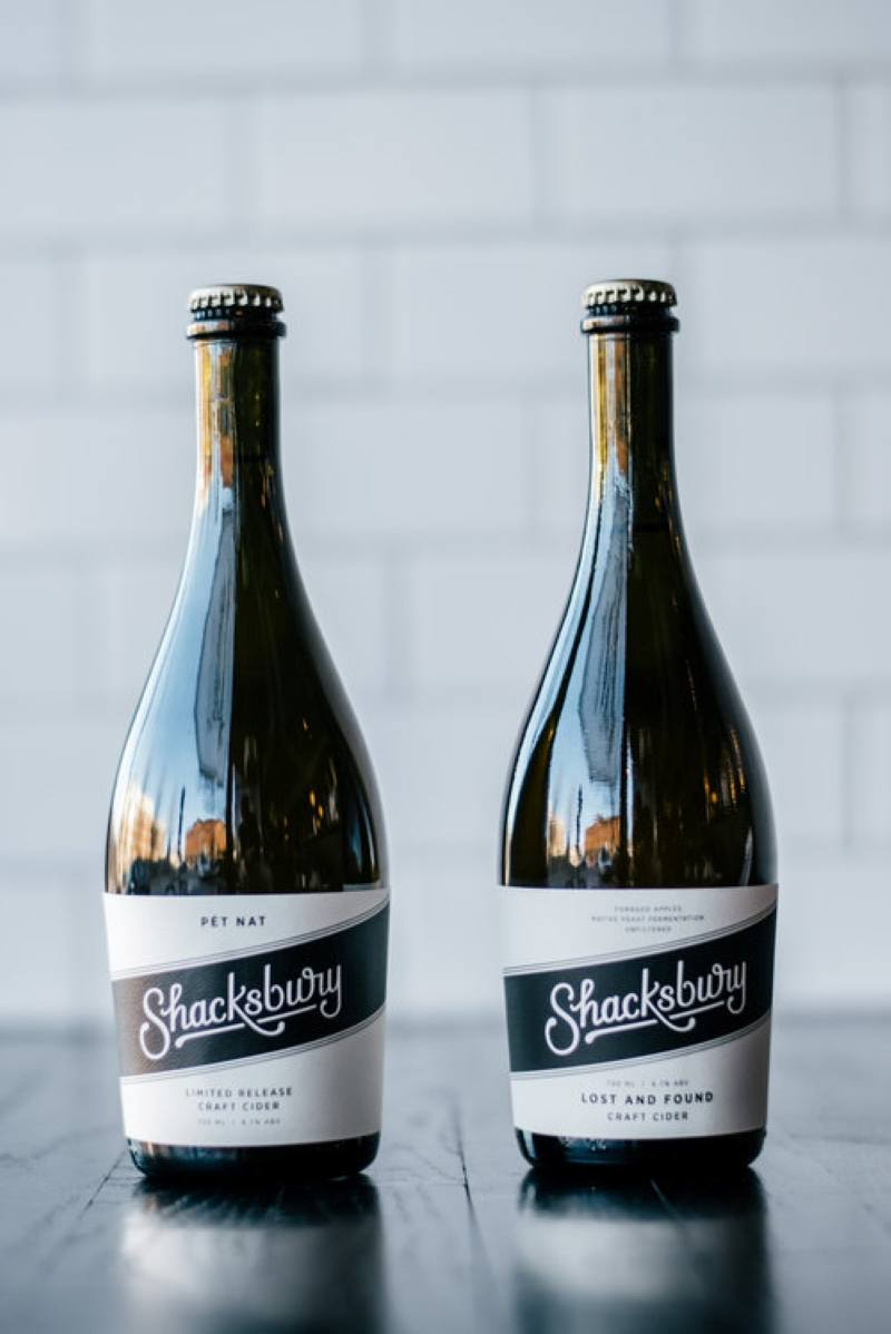 Two large bottles of Shacksbury Craft Cider, sitting on a dark table with a white brick background