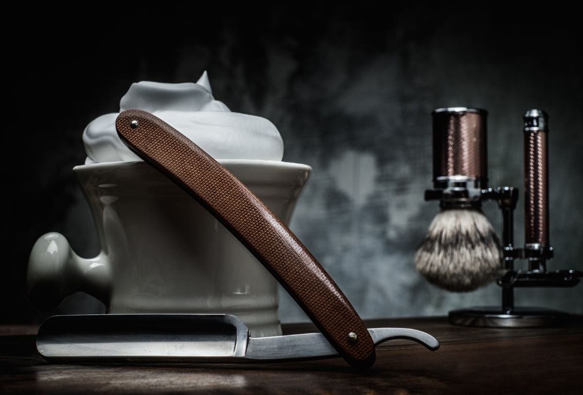 Shave of the Month Clubs- Straight shaving razor with a bowl with foam and brush hanging nearby with a wooden background