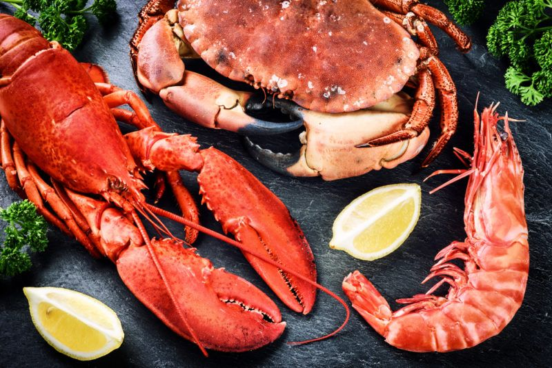 A lobster, a crab and a prawn on a wooden table with lemons