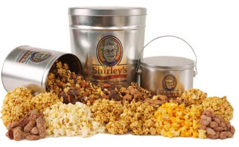Three tins of popcorn.  One lying down with popcorn and nuts spilling out.  Plus, a variety of popcorn and nuts arranged around the base of the picture