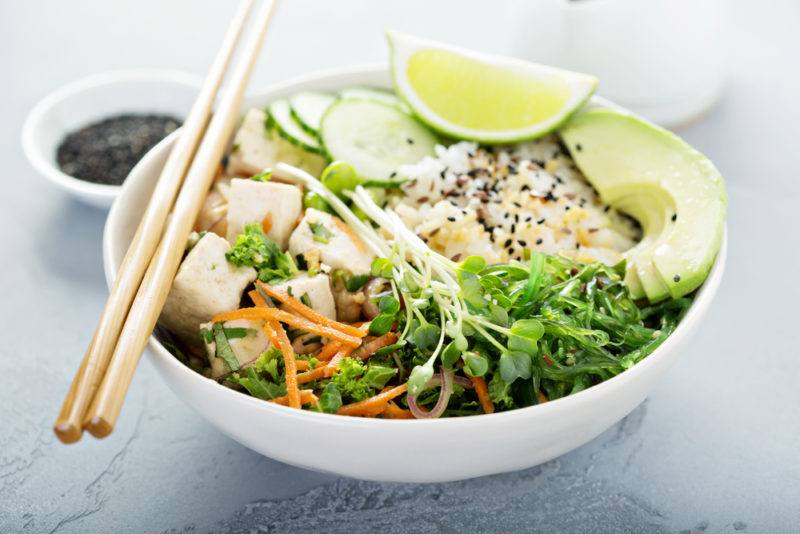 A white bowl that contains tofu, greens, and rice