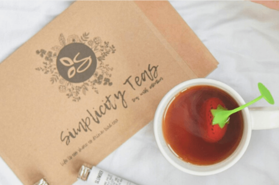 Simplicity tea box in background and a white ceramic tea cup with a strawberry shaped and colored diffuser in a cup of steaming  tea on a white back drop