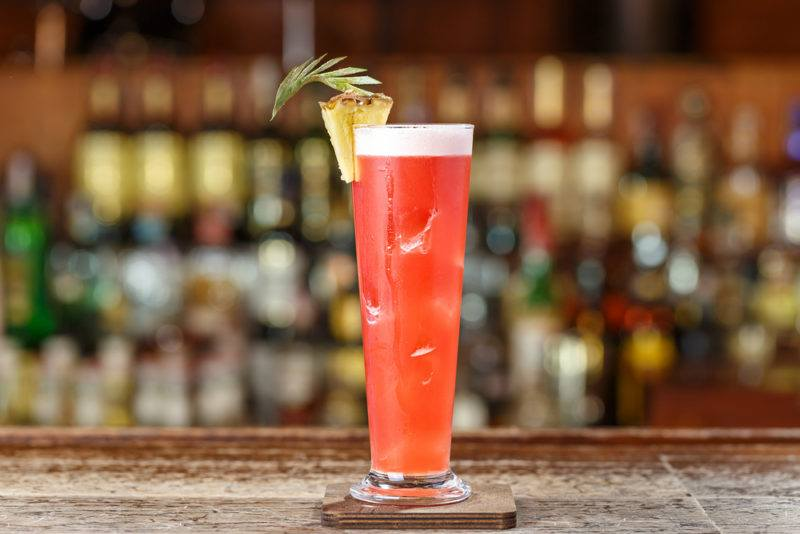 A Singapore Sling cocktail with pineapple garnish on a table