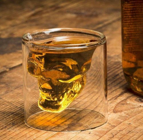 A whiskey glass with a skull shape