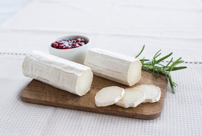Sliced Chèvre cheese and rolls on a cutting board