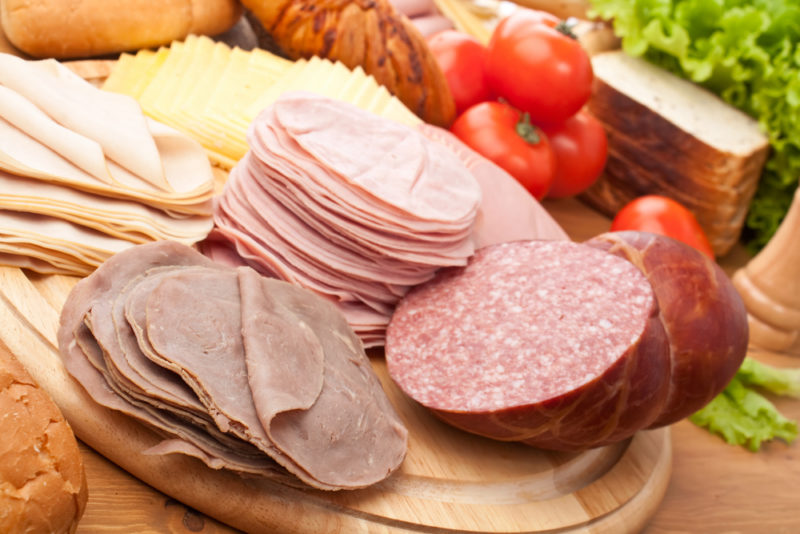 Sliced lunch meat on a board, including beef, ham, chicken, and salami