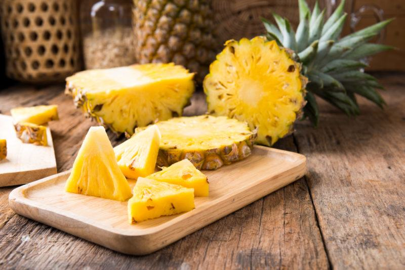A wooden board with sliced pineapple, with the rest of the pineapple in the background