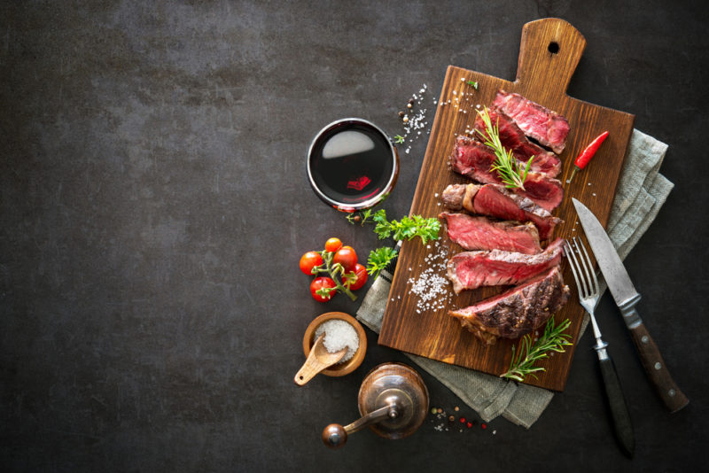A wooden board with sliced rare steak next to a glass of wine, a knife and fork, and seasonings
