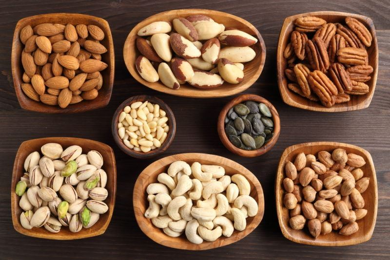 Various small bowls that each contain a different type of nut or seed, including almonds, brazil nuts, and cashews