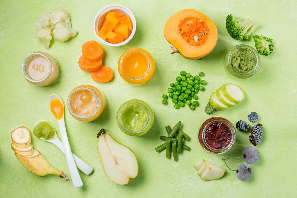 A few containers of baby food next to a large selection of fruits and vegetables