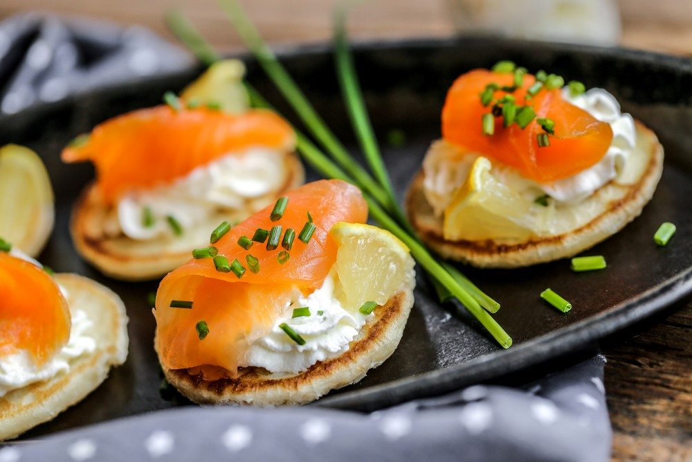 A black plate with small pancakes that have salmon and cream cheese