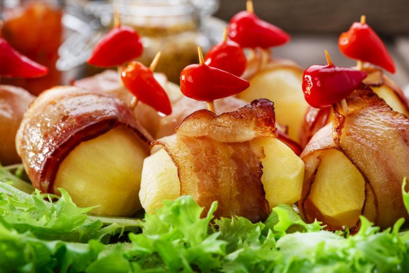 Cooked pieces of potato that have been wrapped in bacon with toothpicks