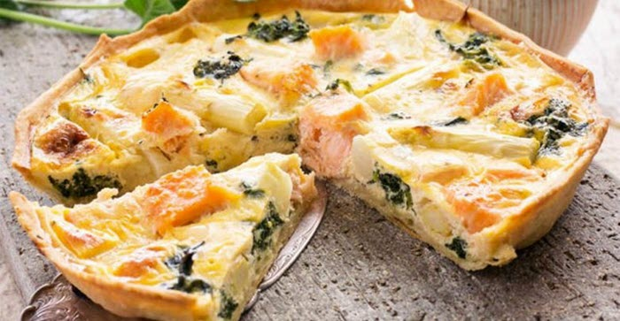 An image of a cut quiche with salmon and leafy greens.
