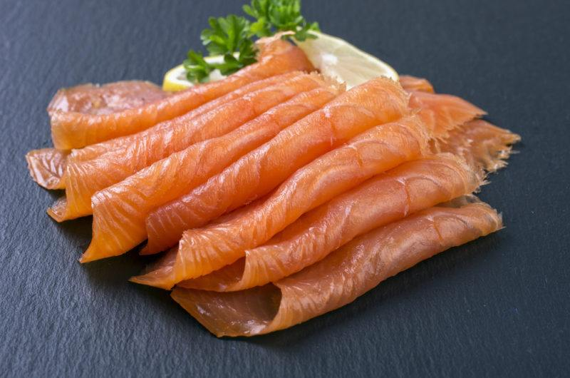 A selection of smoked salmon slices on a gray table with lemon