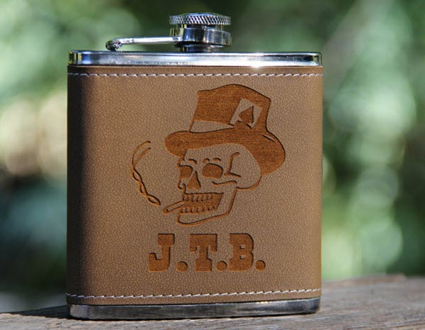 A brown flask with a smoking skull and 3 letters engraved onto it.