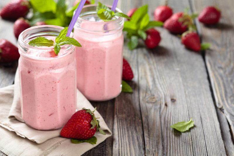 Two strawberry smoothies on a table with fresh strawberries
