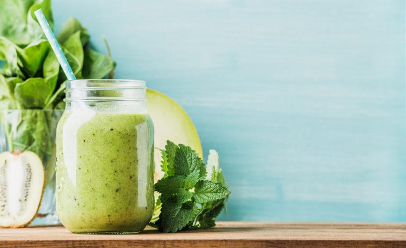 A green smoothie with the ingredients in the background