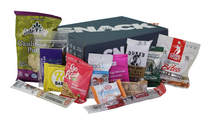 A closed green box with a variety of paleo snacks in front of it