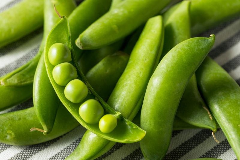 Various snap pea pods on a table with one open showing the contents
