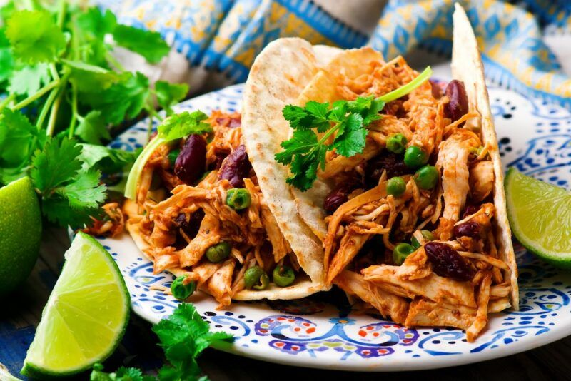 A plate with two soft tacos that have been made with shredded chicken and beans