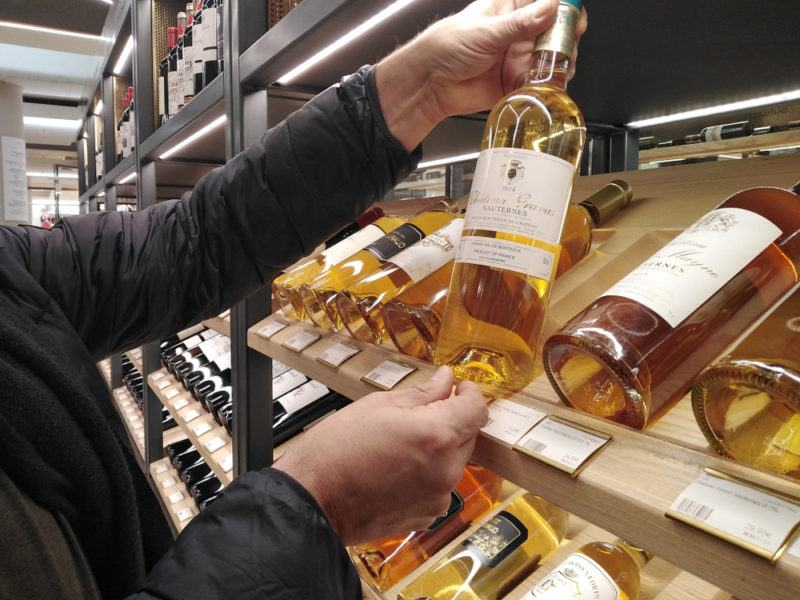 Someone choosing a bottle of sauternes from the shelf that contains many different bottles of the wine