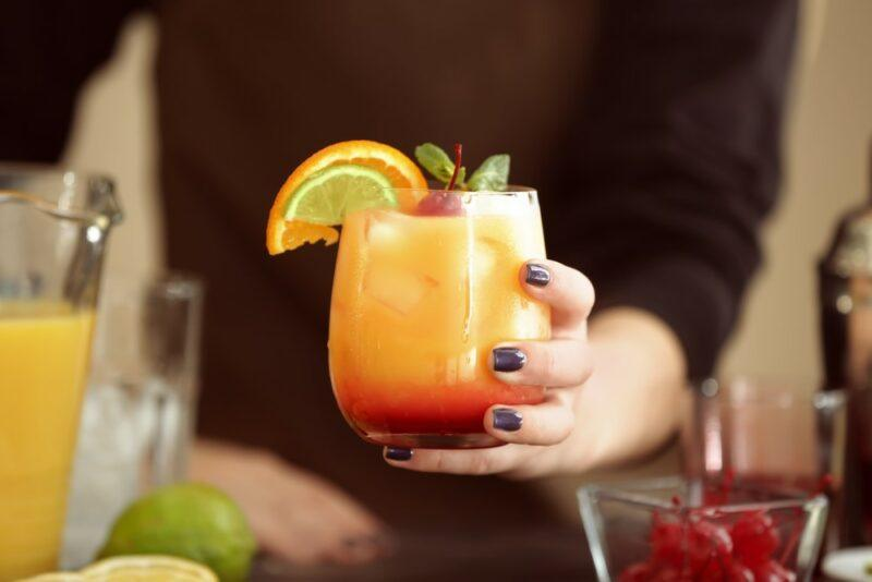 Someone holding a Kentucky sunrise cocktail with red along the bottom