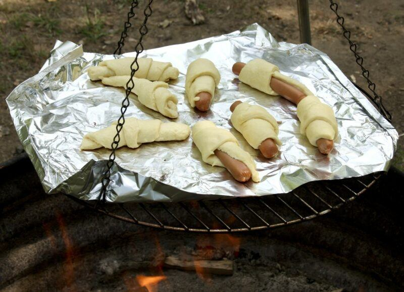 A frame with tinfoil over a fire being used to cook pigs in a blanket