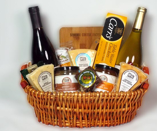 A gift basket containing cheese, mustard and wine.