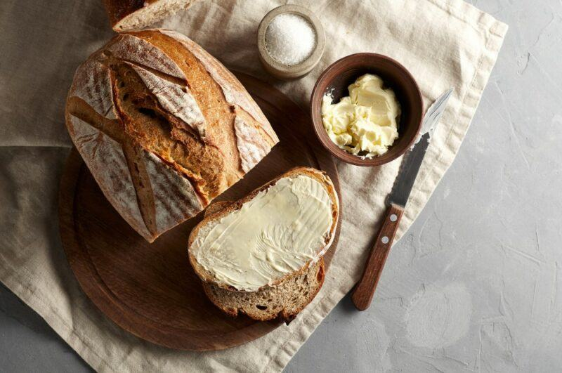 A loaf of sourdough bread, with one slice of bread buttered, next to a small jar butter