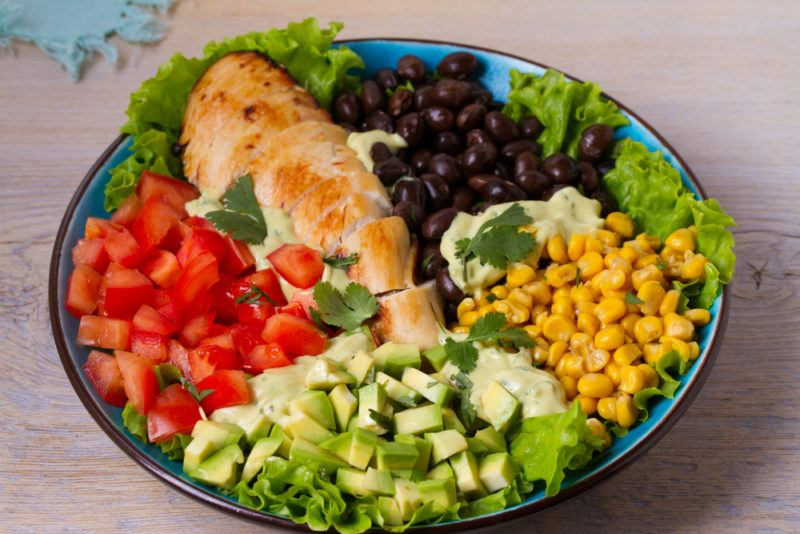 A blue bowl with sliced chicken, peppers, corn, and other ingredients