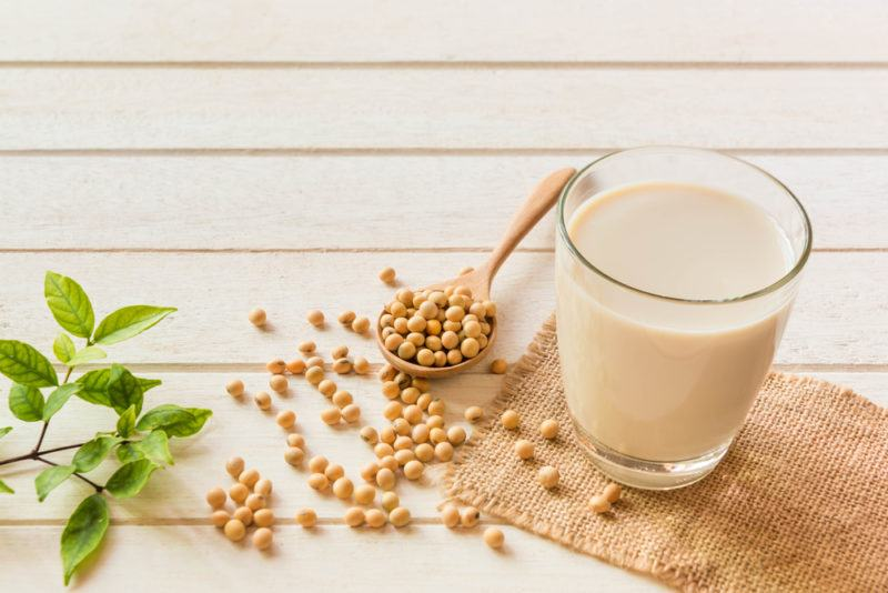 A glass of soy milk with soybeans on a light wooden table