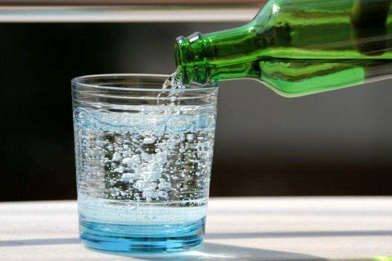 A green bottle of sparking mineral water pouring into a glass