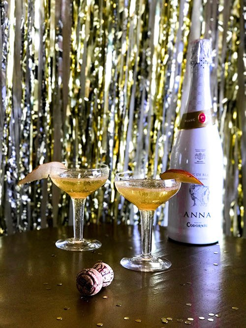 Two cocktails and a bottle of alcohol against a party background